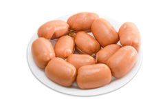 Uncooked sausages in natural casing on a plate Stock Photography
