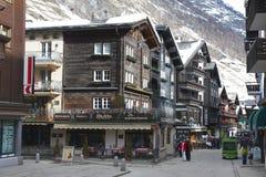 Unidentified tourists explore traditional wooden houses street in Zermatt, Switzerland. Royalty Free Stock Image