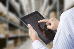 Uomo d'affari che controlla inventario nella stanza di riserva di un'azienda manifatturiera sulla compressa Fotografia Stock
