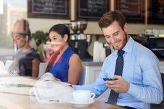 Uomo d'affari With Mobile Phone e giornale in caffetteria Immagini Stock