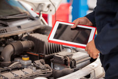 Using tablet computer in auto shop Stock Photography