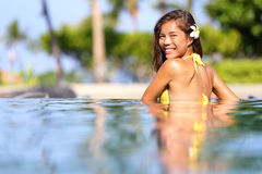 Vacation getaway woman swimming in a tropical pool Stock Photos