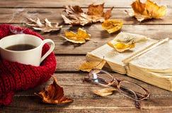 Varma kaffe, bok, exponeringsglas och höstsidor på wood bakgrund Royaltyfri Fotografi