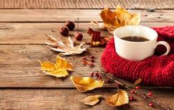 Varma kaffe och höstsidor på tappningträbakgrund Arkivfoton