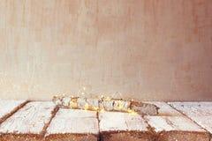 Vecchio ceppo dell'albero con le luci di natale leggiadramente sulla tavola di legno Fuoco selettivo Esposizione del prodotto Fotografia Stock
