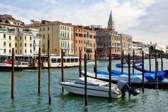 Venedig, Italien Parkmotorboot und Gondeln nahe hölzernen Beiträgen Lizenzfreie Stockfotografie