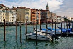 Venedig, Italien Parkmotorboot und Gondeln nahe hölzernen Beiträgen Stockbilder