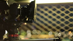 Video dslr camera advancing on slider with beatiful lights in background. behind the scenes video production stock video