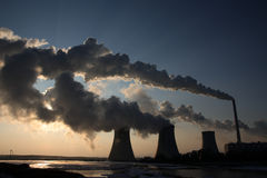 View of coal powerplant against sun and huge fumes Royalty Free Stock Photo