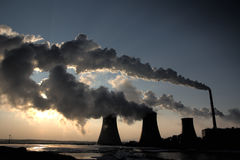 View of coal powerplant against sun and huge fumes Royalty Free Stock Images