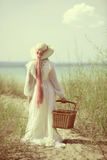 Vintage woman at the beach with picnic basket Stock Photography