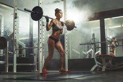Vrouw die barbell met gewicht in gymnastiek opheffen Stock Afbeelding