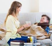 Vrouw die jonge echtgenoot met verwarmingspijp thuis behandelen Royalty-vrije Stock Fotografie