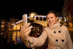 Vrouw die selfie dichtbij Rialto-Brug in Kerstmis Venetië nemen Stock Foto