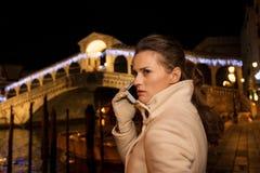 Vrouw het spreken cellphone terwijl het doorbrengen van Kerstmistijd in Venetië Royalty-vrije Stock Foto's