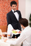 Waiter serving a meal Royalty Free Stock Images