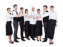 Waiters and waitresses showing thumbs up sign Stock Photo