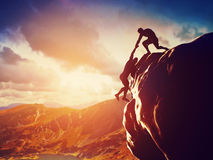 Wandelaars die op rots beklimmen, hand geven en helpen te beklimmen Royalty-vrije Stock Foto