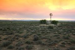 Water Pump Windmill on Arid Farmland Royalty Free Stock Image