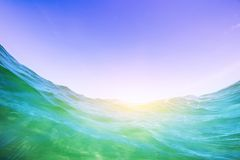 Water wave in the ocean. Underwater and blue sunny sky. Royalty Free Stock Images