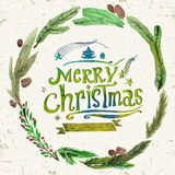 Watercolor Christmas greeting card with wreath of holly twigs and text Merry Christmas. Watercolor art. Christmas decor. Stock Photos