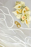 Wedding rings and flowers over veil Stock Photography