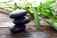 Wet Black Polished Massage Stones Balanced in Spa Stock Photo