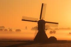 Windmill foggy morning Stock Image
