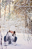 Winter portrait of cute happy child girl in grey fur coat plays with snow in forest Royalty Free Stock Photos