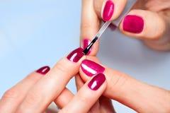 Woman applying nail varnish to finger nails Stock Photography