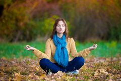 Woman in beige sweater, blue jeans and scarf  meditation Stock Photo