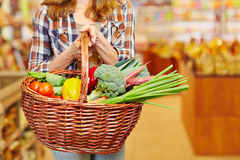 Woman carrying shopping basket in supermarket Stock Image