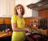 Woman cooks meat Stock Images