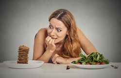 Woman deciding whether to eat healthy food or sweet cookies she craving Royalty Free Stock Photography