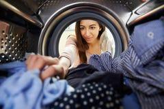 Woman Doing Laundry Reaching Inside Washing Machine Stock Image