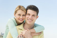 Woman Embracing Man From Behind Against Clear Sky Stock Image