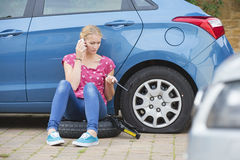 Woman With Flat Tyre On Car Phoning For Assistance Stock Image