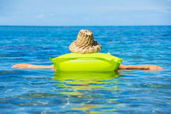 Woman floating on raft in tropical ocean Royalty Free Stock Photo