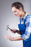 Woman with hammer and spike Stock Images