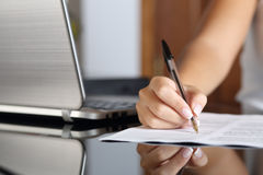 Woman hand writing a contract with a laptop beside Royalty Free Stock Images