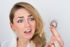 Woman holding loss hair Stock Images