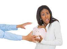 Woman holding piggy bank, frustrated trying to protect her savings Stock Photo