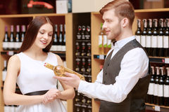 Woman interacts with a sommelier in shop Royalty Free Stock Image