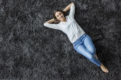 Woman laying on the carpet Stock Image