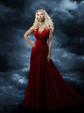 Woman in red dress, long hair blonde in fashion evening gown ove Royalty Free Stock Image