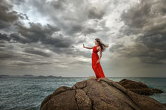 Woman in red dress stands on a cliff with a beautiful sea view a Royalty Free Stock Photo