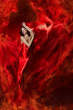 Woman in red waving dress as fire flame Stock Photos