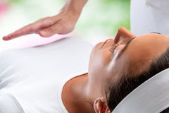 Woman at reiki session with therapist hand in background. Royalty Free Stock Images