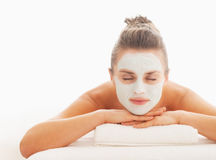 Woman with revitalising mask on face laying on massage table Stock Images