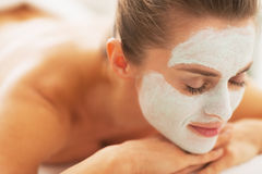 Woman with revitalising mask on face laying on massage table Royalty Free Stock Photo